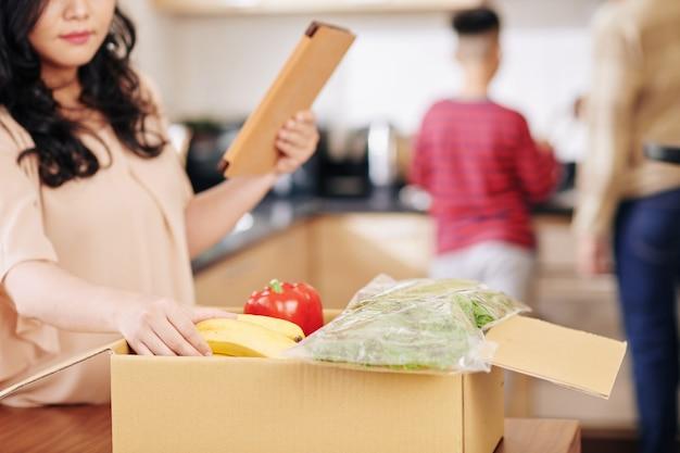 Casalinga con computer tablet prendendo generi alimentari freschi da una grande scatola di cartone quando suo marito e suo figlio preadolescenziale cucinano in background