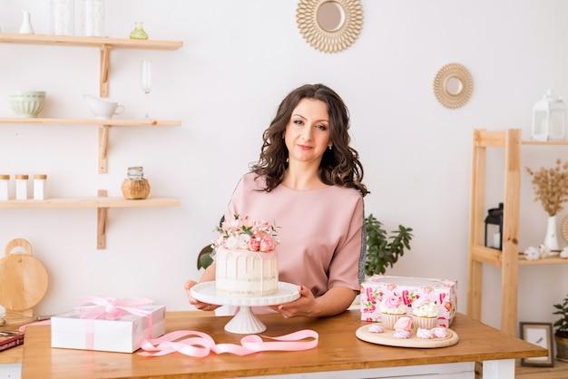 Una casalinga una donna pasticcera in cucina ha preparato una torta e un dolce dessert