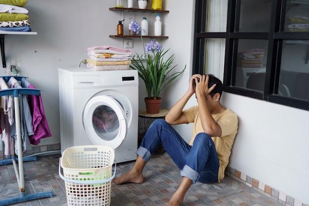 Lavori di casa. stressato uomo asiatico che fa il bucato a casa caricamento di vestiti in lavatrice