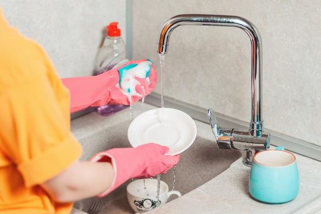 Lavori di casa. una donna con guanti di gomma rosa sta lavando i piatti. vista dalle spalle