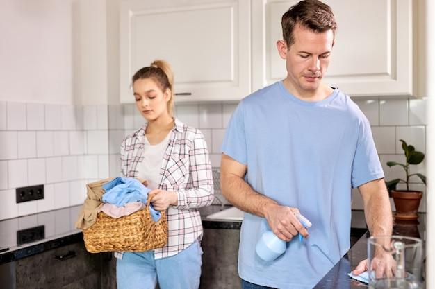 Lavori domestici, giovane coppia sposata a casa, pulizia della cucina con detersivi, andare a lavare le cose. uomo e donna caucasici in abbigliamento casual che fanno le faccende domestiche. focus sull'uomo