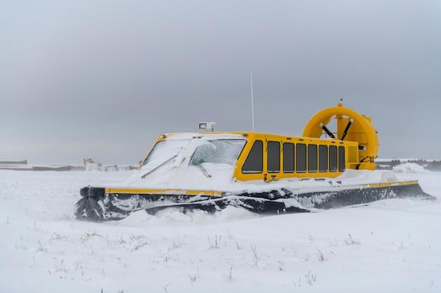 Hovercraft nella tundra invernale. cuscino d'aria sulla spiaggia. imbarcazione gialla al passaggio del mouse sotto la neve.