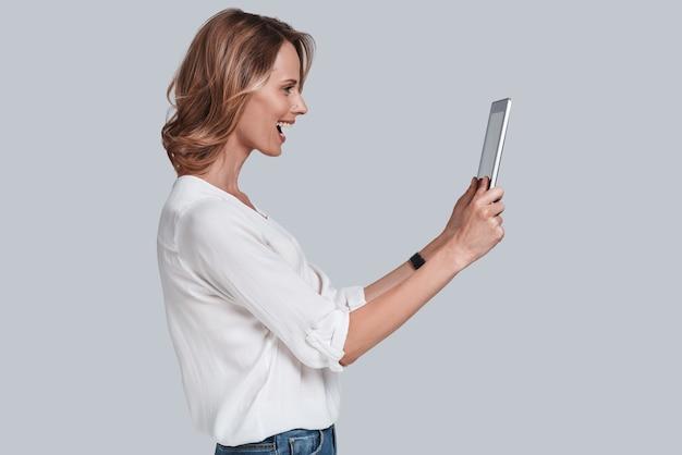 Come stai? bella giovane donna che guarda il tavolo digitale e tiene la bocca aperta mentre sta in piedi su uno sfondo grigio