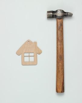 Come costruire una casa? concetto fai da te. figurina della mini casa e del martello su priorità bassa bianca