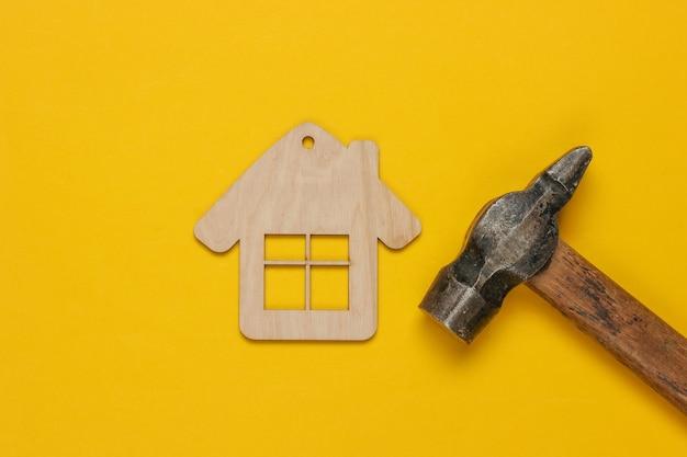 Come costruire una casa? concetto fai da te. figurina di martello e mini casa su sfondo giallo