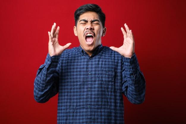 Come hai potuto? ritratto di uomo asiatico frustrato infastidito in piedi con le mani alzate, chiedendo perché. studio al coperto su sfondo rosso