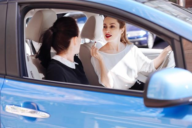 Come ti sembro. donna di affari attraente piacevole positiva che tiene un rossetto e guardando il suo collega mentre chiede la sua opinione sull'aspetto