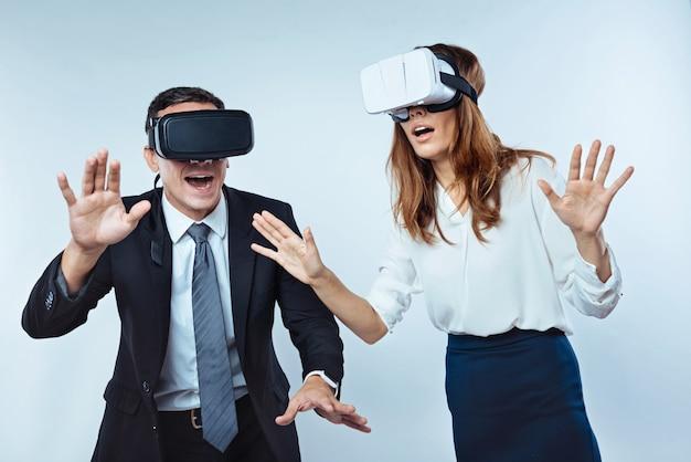 Come è possibile. colleghi sorpresi in piedi con la bocca spalancata mentre entrambi provavano occhiali per realtà virtuale 3d e si eccitavano.
