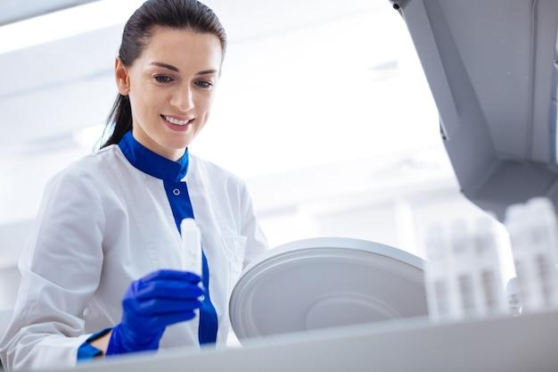Come funziona. giovane scienziato femminile abbastanza piacevole che prepara per ottenere i test mentre trasporta il contenitore e guarda verso il basso