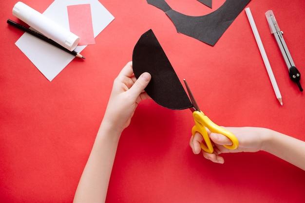 Come fare pipistrello di carta a casa. mani che fanno mestiere di carta. istruzioni fotografiche passo dopo passo. passaggio 3. tagliare i cerchi in due parti. progetto artistico fai-da-te per bambini