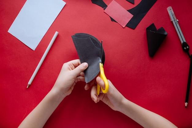 Come fare pipistrello di carta a casa. mani che fanno mestiere di carta. istruzioni fotografiche passo dopo passo. passaggio 7. tagliare le ali. progetto artistico fai-da-te per bambini.