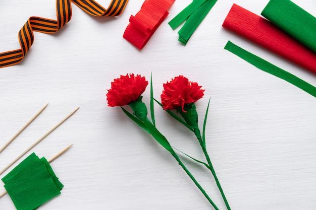 Come fare il fiore del garofano a casa. mani che fanno garofano rosso per il giorno della vittoria 9 maggio. istruzioni passo passo. passaggio 17. il fiore è pronto. progetto artistico fai-da-te per bambini. 20apr2020 san pietroburgo russia