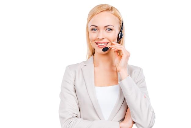 Come posso aiutarti? rappresentante del servizio clienti maturo fiducioso che regola le cuffie e sorride mentre si trova in piedi su sfondo bianco