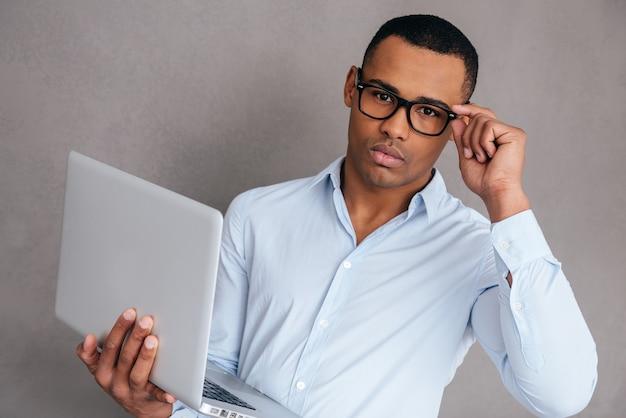 Come posso aiutarti? fiducioso giovane africano che trasporta laptop e