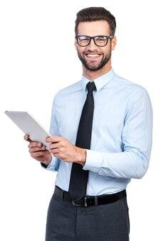 Come posso aiutarti? fiducioso giovane bell'uomo in camicia e cravatta che tiene in mano un tablet digitale e guarda la telecamera con un sorriso mentre si trova su sfondo bianco