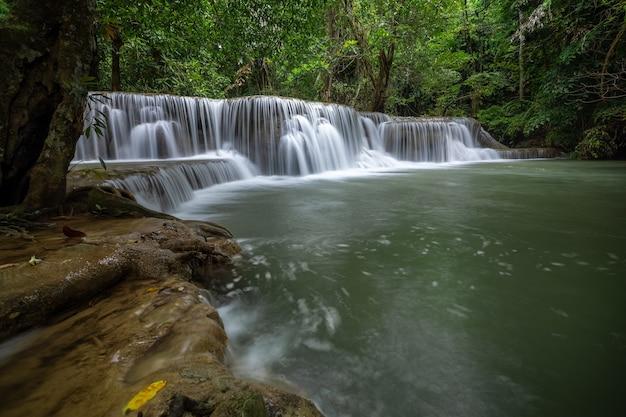 La cascata di hua mea khamin ha alberi tropicali, felci, crescita sulla cascata al mattino