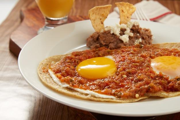 Huevos rancheros con salsa picante roja y frijoles refritos desayuno tipico mexicano