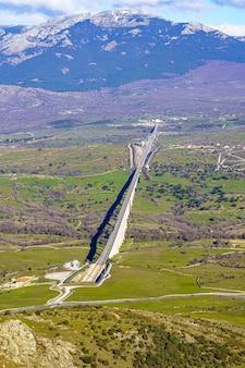 Enorme ponte in montagna per il passaggio del treno ad alta velocità con un tunnel in fondo che entra nella montagna. madrid.