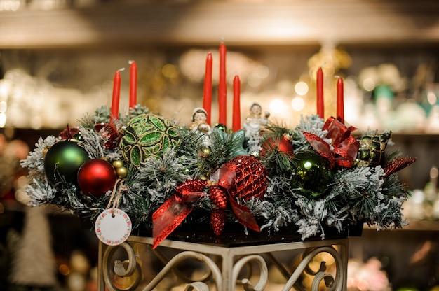 Enorme composizione natalizia di rami di abete innevati, candele, nastri, palline rosse e verdi e bambini giocattolo