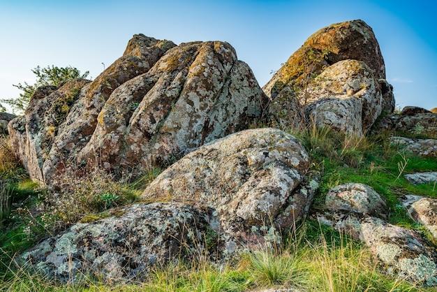 Enormi depositi di vecchi minerali di pietra ricoperti di vegetazione in un prato pieno di caldo sole in ucraina e nella sua splendida natura