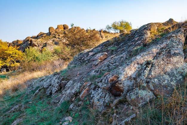 Enormi depositi di minerali di pietra antichi ricoperti di vegetazione in un prato pieno di caldo sole in ucraina e nella sua bellissima natura