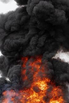 Enormi fiamme di fuoco rosso-arancio, nuvole in movimento di cielo coperto di fumo scuro