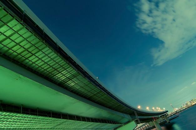 Enorme struttura autostradale che va lontano sopra le acque del fiume notturno a tokyo, giappone