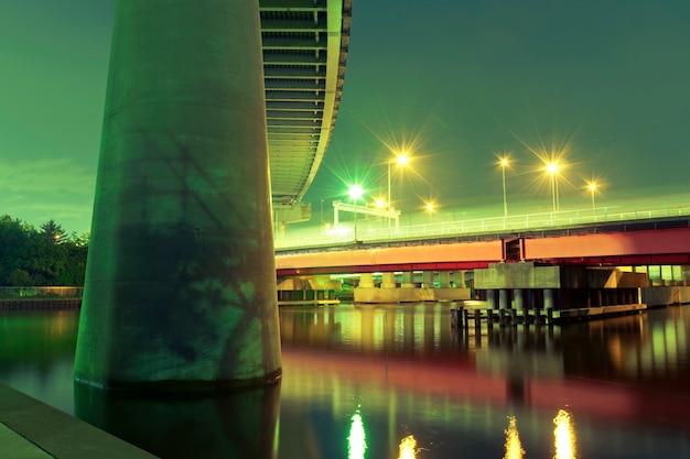 Enorme supporto autostradale in primo piano con ponte rosso illuminato di notte a tokyo, giappone