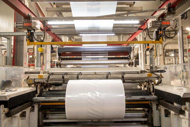 Enorme macchina industriale con grande pellicola di polietilene trasparente di nuova produzione nell'officina della fabbrica