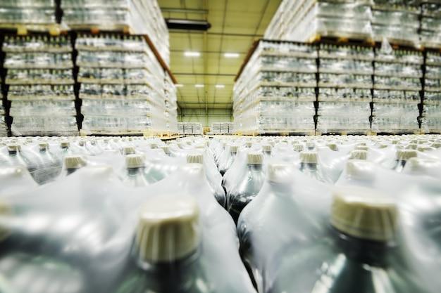Un enorme magazzino industriale con involucro di plastica per alimenti avvolto in bottiglie di plastica con bevande gassate, acqua o birra.