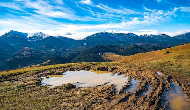 Un'enorme pozza fangosa con fango disgustoso su un piccolo sentiero nelle montagne dei carpazi sullo sfondo di splendide colline autunnali