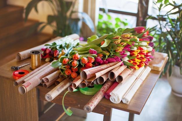 Un enorme mazzo multicolore di tulipani si trova su un tavolo in un negozio di fiori