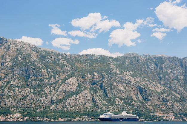 Un'enorme nave da crociera a più ponti nella baia di kotor, sullo sfondo di una montagna sopra la città