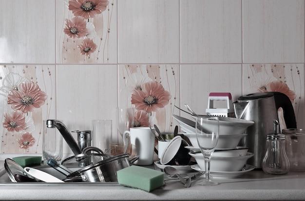 Un enorme mucchio di piatti non lavati nel lavandino della cucina e sul bancone