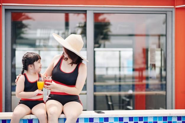 Abbracciare madre e figlia seduti sul bordo della piscina e bere cocktail di frutta fresca