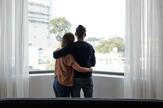 Abbracciando una giovane coppia in piedi davanti alla grande finestra e guardando fuori, vista dal retro
