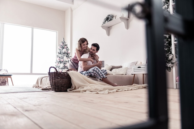 Abbracci. donna bionda dai capelli lunghi che abbraccia il suo marito bruna mentre trascorre una mattinata insieme
