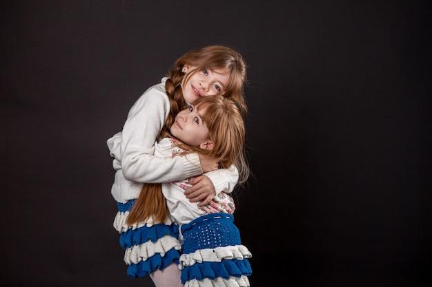 Abbracci di due sorelle ragazze. amore in famiglia, relazioni con i bambini. abbraccio bambini