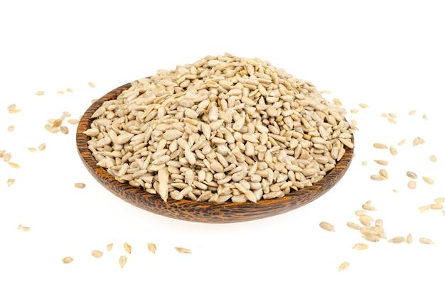 I semi di girasole hullled si accumulano nella ciotola sulla superficie bianca