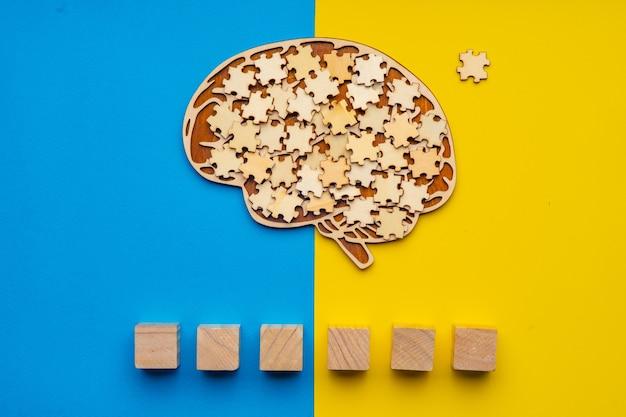 Cervello umano con pezzi di un puzzle sparsi su un giallo e blu. sei cubi in cui puoi scrivere la parola autismo nel tuo carattere.