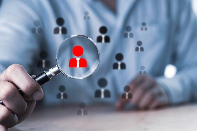 Lo sviluppo umano e il concetto di reclutamento, uomo di affari che utilizza la lente di ingrandimento alla ricerca di dipendenti adeguati.