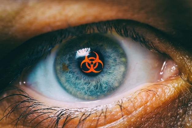 Occhio umano con segnale di rischio biologico. simbolo di infezione, epidemia