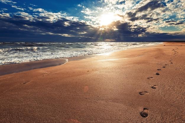 Impronte umane su una spiaggia di mare deserta