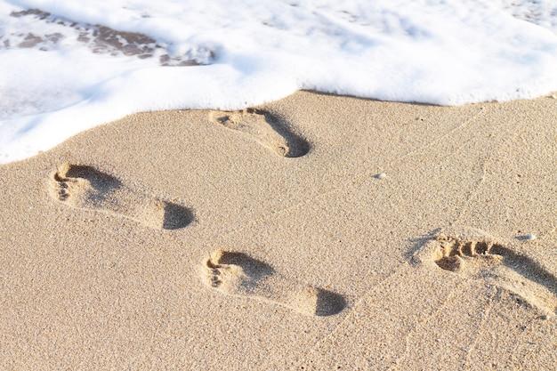 Impronte umane sulla spiaggia sabbiosa con onde del mare