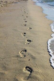 Orme umane su una spiaggia sabbiosa del mare che si estende in lontananza. a destra le onde si infrangono sulla riva