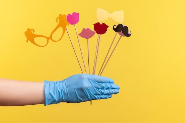 Mano umana in guanti chirurgici blu che tengono e mostrano molte diverse cabine fotografiche in mano