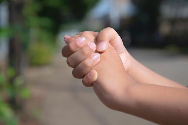 Mano umana che tiene un'altra mano con sfondo sfocato
