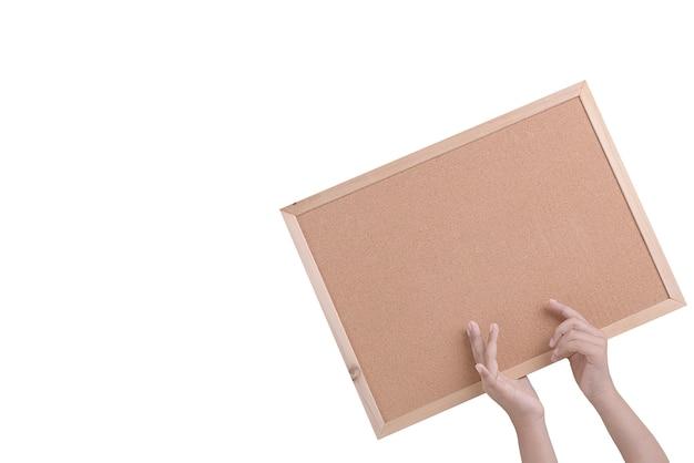 Mano umana che tiene una bacheca di sughero marrone in una cornice isolata sopra il muro bianco