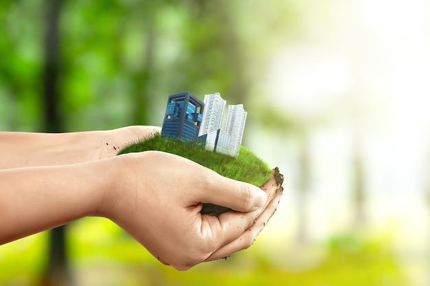 Mano umana che tiene terra con edifici e appartamenti. giornata mondiale dell'habitat