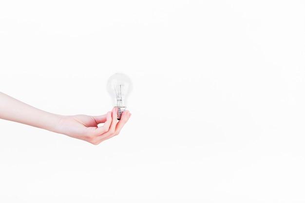 Mano umana che tiene lampadina su priorità bassa bianca
